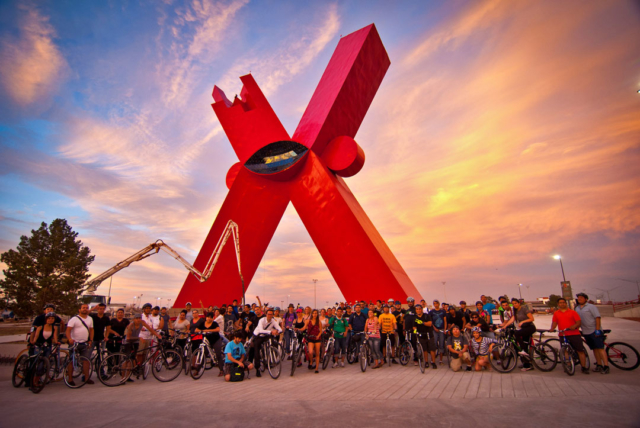 view of a group of cyclists from juarez and le paso and the x sculpture on the background